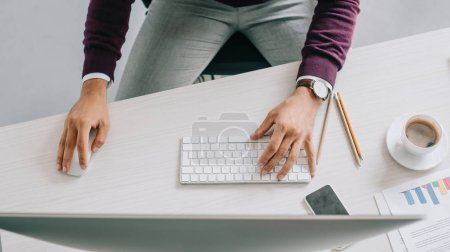 cropped image of designer working at table with computer in office