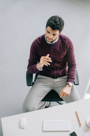 Photo for High angle view of pensive handsome designer in burgundy sweater sitting at table in office - Royalty Free Image