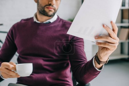 cropped image of designer with bristle holding cup of coffee and reading documents in office