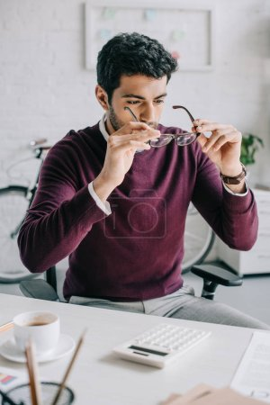 handsome designer in burgundy sweater wearing glasses in office