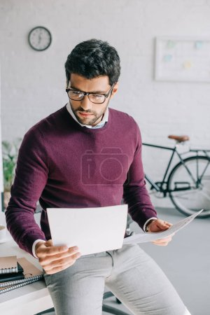 handsome businessman in burgundy sweater leaning on table and reading documents in office