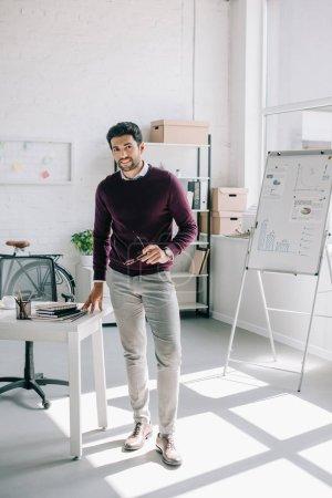 Photo pour Sourire de beau homme d'affaires en chandail Bourgogne tenant des lunettes et regardant la caméra dans le Bureau - image libre de droit