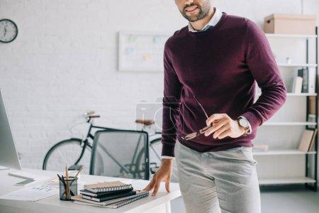 Photo pour Image recadrée d'homme d'affaires souriant en chandail Bourgogne tenant des lunettes au bureau - image libre de droit