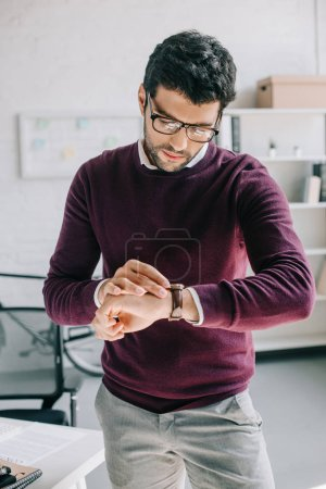 handsome designer in burgundy sweater checking time at wristwatch in office