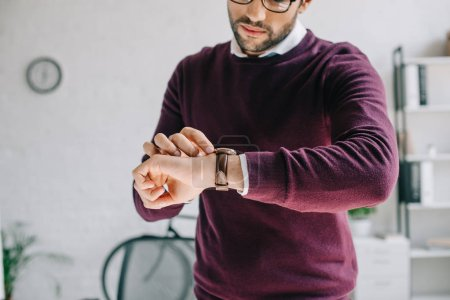 cropped image of designer in burgundy sweater checking time at wristwatch in office