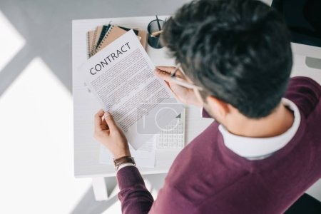 overhead view of designer in burgundy sweater reading contract in office