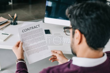 back view of businessman reading contract in office