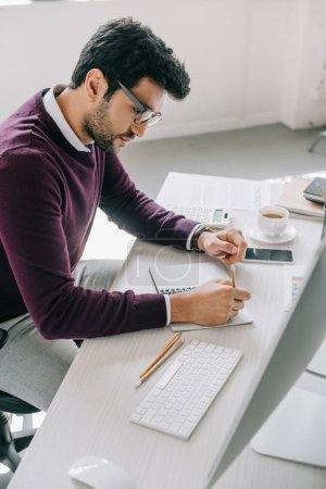 side view of handsome designer in burgundy sweater making sketch in notebook in office
