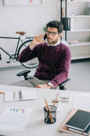 handsome designer in burgundy sweater talking by smartphone in office
