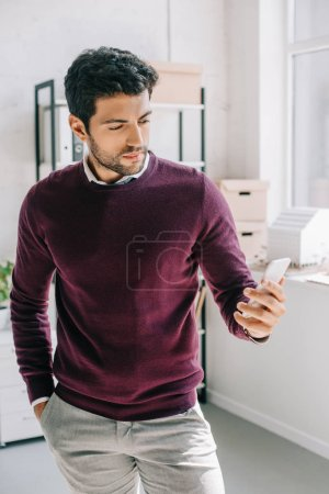 Photo for Handsome designer in burgundy sweater looking at smartphone in office - Royalty Free Image