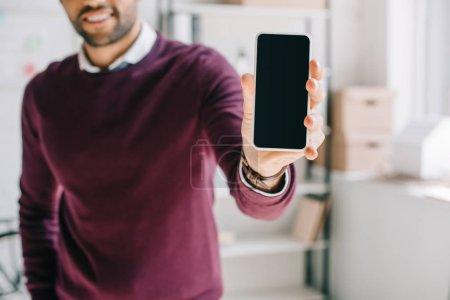 Photo pour Cropped image du concepteur souriant de chandail Bourgogne montrant smartphone avec écran blanc au bureau - image libre de droit