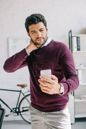 Photo pour Bel homme d'affaires en chandail Bourgogne regardant smartphone au bureau - image libre de droit
