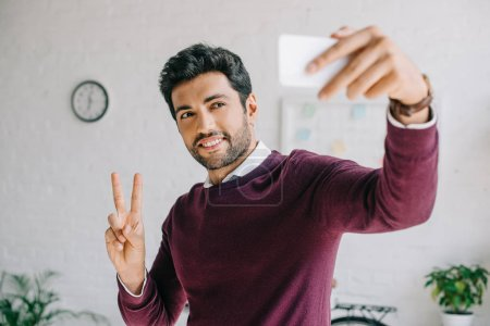 smiling businessman in burgundy sweater taking selfie with smartphone and showing two fingers in office