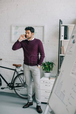 handsome designer in burgundy sweater talking by smartphone in office and looking away