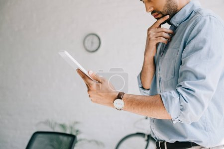 cropped image of pensive architect using tablet in office