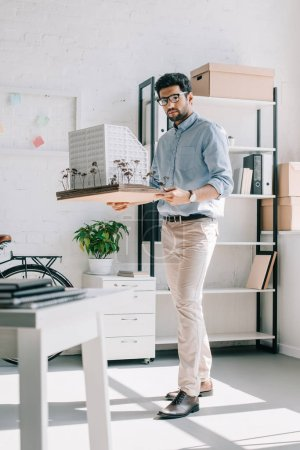 handsome architect holding architecture model in office