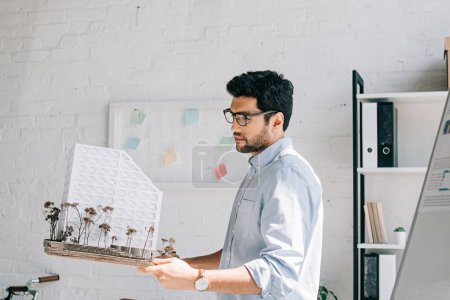 Photo for Side view of handsome architect in glasses holding architecture model in office - Royalty Free Image