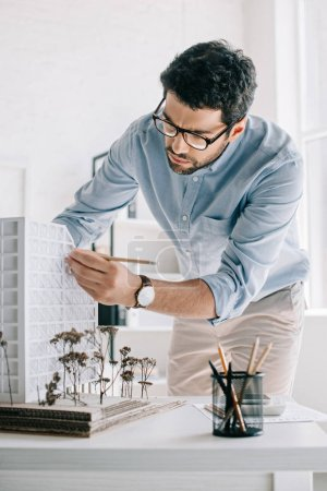 Photo for Handsome architect working with architecture model on table in office - Royalty Free Image