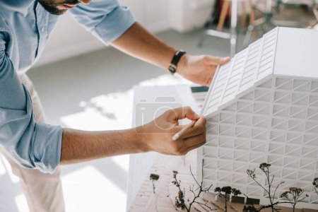 cropped image of architect working with architecture model on table in office