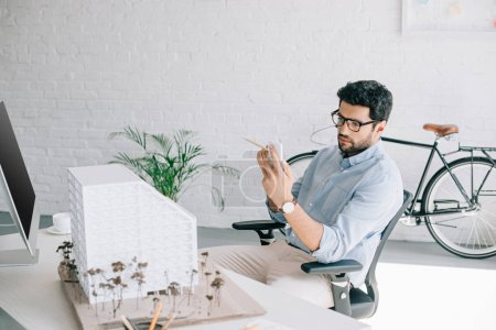 handsome architect using smartphone near architecture model in office