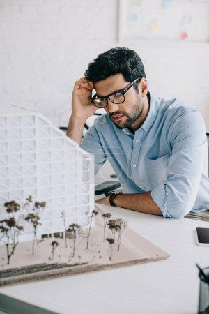 architecte bouleversé, modèle d'architecture au bureau en regardant