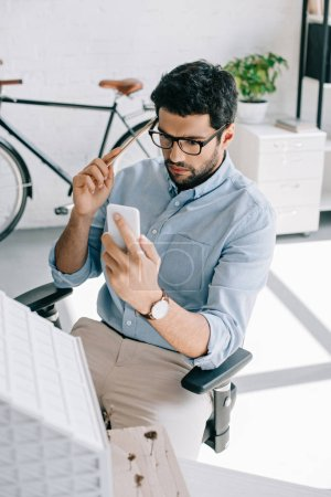 serious architect using smartphone near architecture model in office