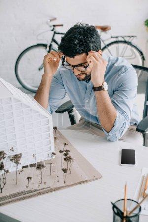 Foto de Apuesto arquitecto tocando la cabeza y mirar el modelo de arquitectura en oficina - Imagen libre de derechos