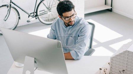 Photo pour Beau architecte utilisant l'ordinateur et en regardant de modèle au bureau d'architecture - image libre de droit