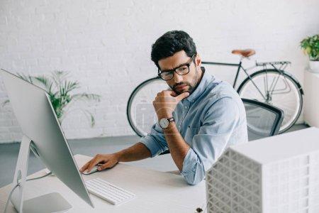 Foto de Seria guapo arquitecto utiliza equipo y mirando en el modelo de arquitectura en oficina - Imagen libre de derechos