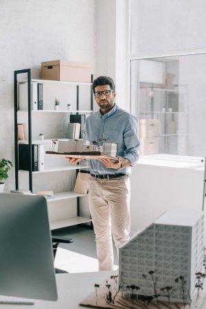 Photo pour Beau architecte tenant modèle d'architecture au bureau et en regardant la caméra - image libre de droit