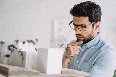 Foto de Apuesto arquitecto pensativo en gafas mirando el modelo de arquitectura en oficina - Imagen libre de derechos