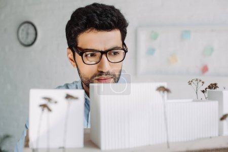 Photo for Handsome brunette architect in glasses looking at architecture model in office - Royalty Free Image
