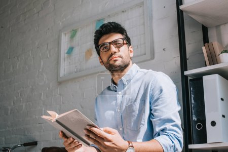 Photo for Handsome architect in glasses holding book and looking away in office - Royalty Free Image
