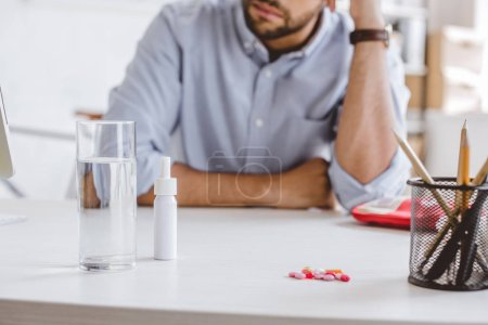 Photo for Cropped image of sick manager leaning on table with medicines in office - Royalty Free Image