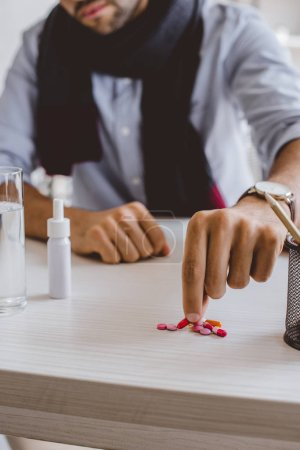 cropped image of sick manager in scarf taking pill from pile in office