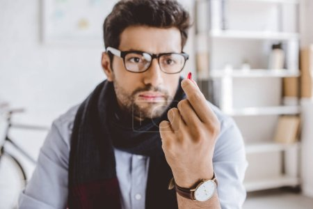 sick manager in scarf looking at pill in office