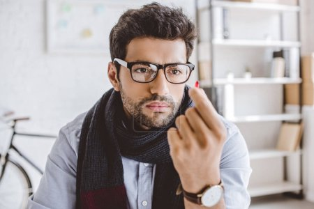 sick manager in scarf and glasses looking at pill in office