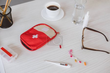 first aid kit, cup of coffee and pills on table in office
