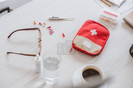 high angle view of first aid kit, glass of water, cup of coffee and pills on table in office