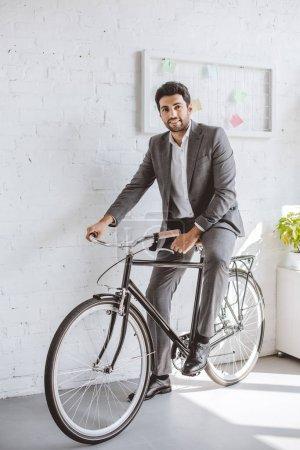 Photo pour Homme d'affaires souriant assis sur le vélo dans le bureau et regardant la caméra - image libre de droit
