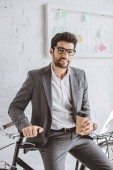 smiling handsome businessman holding cup of coffee and leaning on bike in office