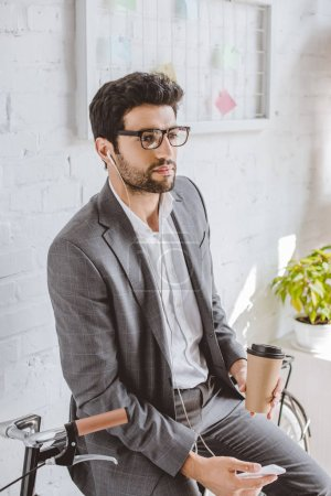 businessman listening music with smartphone, holding coffee in paper cup and leaning on bike in office