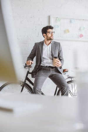 handsome businessman sitting on bike and holding coffee to go in office