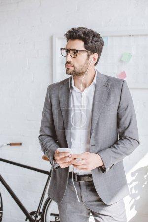 Photo pour Musique écoute bel homme d'affaires avec smartphone et à la recherche de suite au bureau - image libre de droit