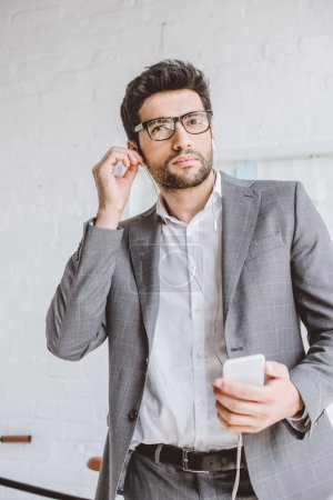 handsome businessman plugging earphones to listening music in office