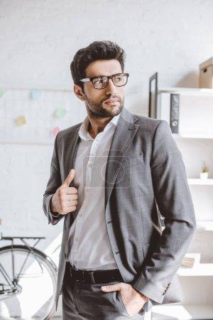 Foto de Hombre de negocios guapo en traje gris mirando lejos en oficina - Imagen libre de derechos