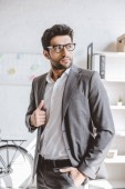 handsome businessman in grey suit looking away in office
