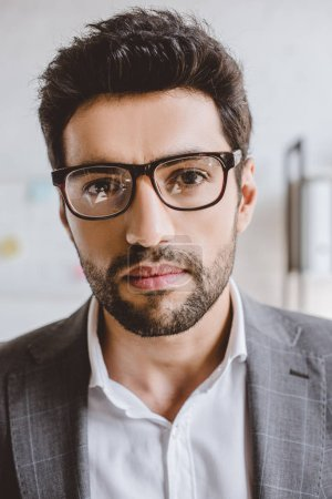 Photo for Portrait of handsome businessman with bristle in glasses looking at camera in office - Royalty Free Image