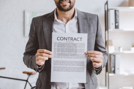 cropped image of cheerful businessman showing contract in office