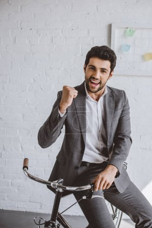 happy handsome businessman sitting on bike and showing yes gesture in office